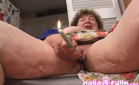 Grandma shoves a candle in her pussy