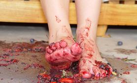 Sexy shoeless feet crushing fresh fruits