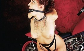 Sexy redhead slave bound to a Harley