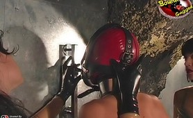 Two dominatrix training on submissive latex slave