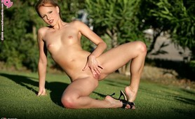 Alluring blonde cutie spreading her pretty pussy on the garden
